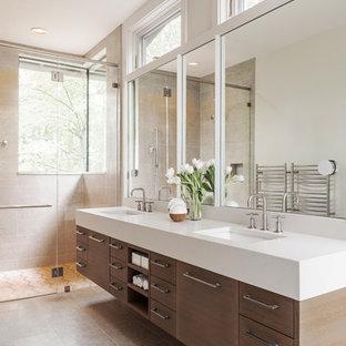 На фото: большая главная ванная комната в стиле кантри с плоскими фасадами, фасадами цвета дерева среднего тона, душем без бортиков, бежевой плиткой, плиткой из известняка, полом из известняка, врезной раковиной, столешницей из искусственного кварца, бежевым полом и душем с распашными дверями