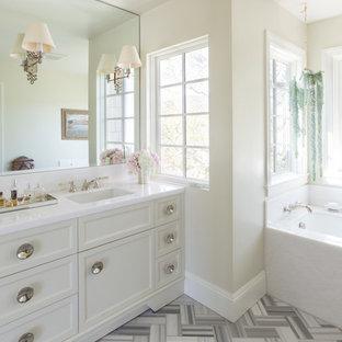 Foto di una stanza da bagno classica con lavabo sottopiano, ante con riquadro incassato, ante bianche, vasca sottopiano e pareti beige