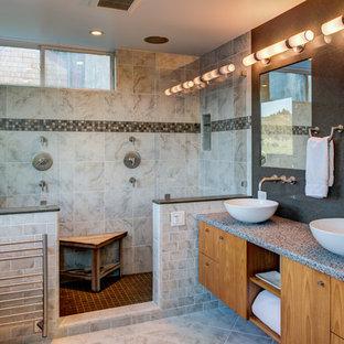 Diseño de cuarto de baño principal, actual, de tamaño medio, con lavabo sobreencimera, armarios con paneles lisos, puertas de armario de madera oscura, encimera de vidrio reciclado, baldosas y/o azulejos grises, baldosas y/o azulejos de piedra, suelo de mármol, ducha doble y paredes grises
