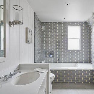 Immagine di una stanza da bagno con doccia american style di medie dimensioni con ante bianche, vasca sottopiano, vasca/doccia, piastrelle grigie, piastrelle gialle, piastrelle diamantate, pareti bianche, lavabo sottopiano, pavimento grigio, top bianco, pavimento in cemento e top in superficie solida