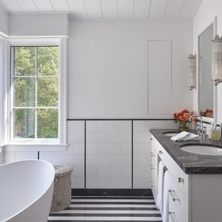 Example of a large arts and crafts master black and white tile, white tile and subway tile multicolored floor and porcelain tile bathroom design in San Francisco with flat-panel cabinets, white cabinets, an undermount sink, black countertops, a two-piece toilet, white walls, marble countertops and a hinged shower door