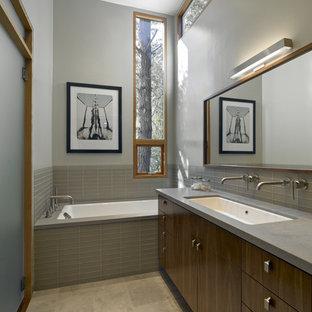 Foto di una stanza da bagno padronale moderna con lavabo rettangolare, ante lisce, ante in legno bruno, vasca sottopiano, piastrelle grigie, piastrelle di vetro, pareti grigie e top in quarzo composito