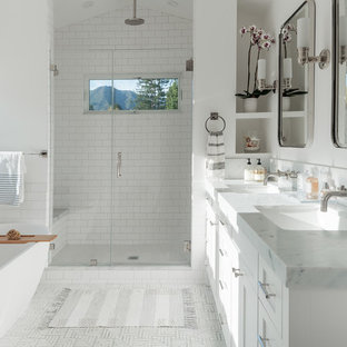 Traditional ensuite bathroom in San Francisco with shaker cabinets, white cabinets, a freestanding bath, an alcove shower, white tiles, metro tiles, white walls, a submerged sink, grey floors and a hinged door.