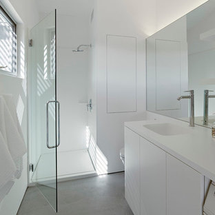 Mid-sized minimalist concrete floor alcove shower photo in San Francisco with an integrated sink, flat-panel cabinets, white cabinets, solid surface countertops, a wall-mount toilet, white walls and white countertops