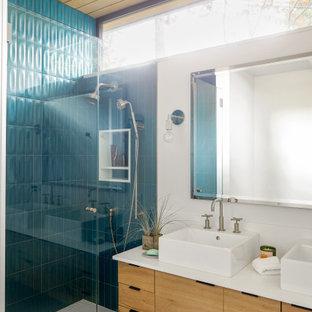 Aménagement d'une salle de bain bord de mer avec un placard à porte plane, des portes de placard en bois clair, meuble double vasque, meuble-lavabo suspendu, un carrelage vert, un mur blanc, un sol en carrelage de terre cuite, une vasque, un sol blanc, une cabine de douche à porte battante, un plan de toilette blanc, une niche et un plafond en bois.