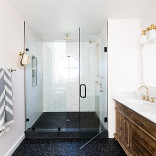Transitional white tile pebble tile floor and black floor alcove shower photo in Sacramento with raised-panel cabinets, brown cabinets, white walls, an undermount sink and a hinged shower door