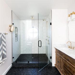Esempio di una stanza da bagno classica con ante con bugna sagomata, ante marroni, doccia alcova, piastrelle bianche, pareti bianche, pavimento con piastrelle di ciottoli, lavabo sottopiano, pavimento nero e porta doccia a battente