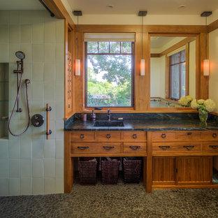 Ejemplo de cuarto de baño de estilo americano, grande, con lavabo integrado, puertas de armario de madera oscura, encimera de mármol, ducha abierta, baldosas y/o azulejos verdes, baldosas y/o azulejos de vidrio, paredes beige y ducha abierta