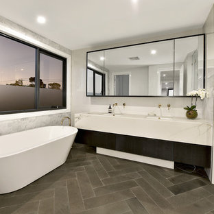 This is an example of a mid-sized contemporary master bathroom in Melbourne with dark wood cabinets, a freestanding tub, a double shower, white tile, ceramic tile, grey walls, ceramic floors, an undermount sink, engineered quartz benchtops, grey floor, a hinged shower door and grey benchtops.