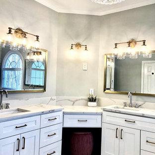 Идея дизайна: большая главная ванная комната в классическом стиле с фасадами в стиле шейкер, белыми фасадами, отдельно стоящей ванной, открытым душем, унитазом-моноблоком, белой плиткой, керамогранитной плиткой, серыми стенами, полом из керамогранита, врезной раковиной, столешницей из кварцита, белым полом, душем с распашными дверями, белой столешницей, сиденьем для душа, тумбой под две раковины, напольной тумбой, кессонным потолком и кирпичными стенами