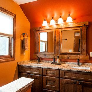 Foto di una stanza da bagno padronale stile rurale di medie dimensioni con lavabo sottopiano, ante in stile shaker, ante in legno scuro, top in granito, doccia alcova, piastrelle beige, piastrelle in ceramica, pareti arancioni e pavimento in gres porcellanato