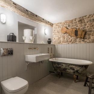 Modelo de cuarto de baño campestre, de tamaño medio, con bañera exenta, sanitario de una pieza, paredes grises, suelo de cemento y lavabo suspendido