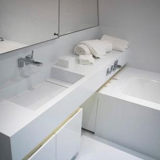 Diseño de cuarto de baño principal, actual, de tamaño medio, con armarios con paneles lisos, bañera exenta, sanitario de pared, baldosas y/o azulejos blancos, puertas de armario blancas, baldosas y/o azulejos con efecto espejo, paredes blancas, suelo vinílico, lavabo integrado y encimera de acrílico