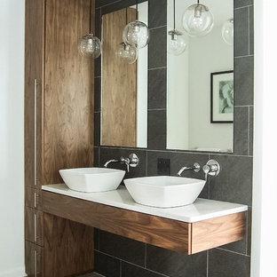 Modern inredning av ett mellanstort en-suite badrum, med grå kakel, bänkskiva i kvartsit, släta luckor, skåp i mellenmörkt trä, keramikplattor, klinkergolv i keramik och ett fristående handfat