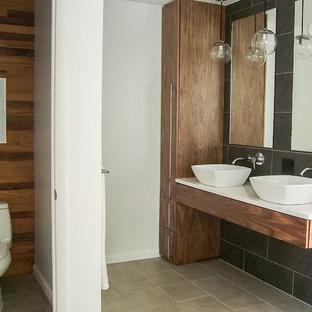 Modelo de cuarto de baño principal, minimalista, de tamaño medio, con baldosas y/o azulejos grises, encimera de cuarcita, armarios con paneles lisos, puertas de armario de madera oscura, bañera exenta, sanitario de una pieza, baldosas y/o azulejos de cerámica, suelo de baldosas de cerámica, lavabo sobreencimera y paredes multicolor