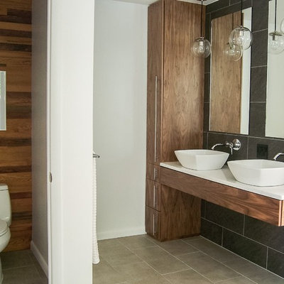 Mid-sized minimalist master gray tile and ceramic tile ceramic tile freestanding bathtub photo in Grand Rapids with quartzite countertops, flat-panel cabinets, medium tone wood cabinets, a one-piece toilet, a vessel sink and multicolored walls