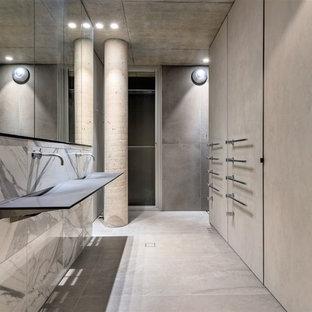 Esempio di una stanza da bagno padronale industriale con piastrelle grigie, piastrelle bianche, pareti grigie, pavimento in cemento, lavabo sospeso, pavimento grigio, ante di vetro, piastrelle in travertino e top in vetro