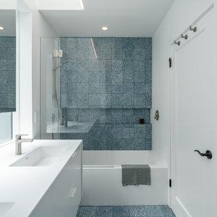 Inredning av ett modernt mellanstort vit vitt badrum för barn, med släta luckor, vita skåp, ett badkar i en alkov, en dusch/badkar-kombination, en vägghängd toalettstol, blå kakel, cementkakel, vita väggar, cementgolv, ett integrerad handfat, bänkskiva i akrylsten och blått golv