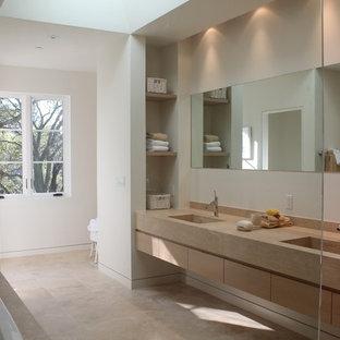 Imagen de cuarto de baño principal, mediterráneo, grande, con lavabo integrado, puertas de armario de madera clara, bañera encastrada, baldosas y/o azulejos beige, baldosas y/o azulejos de piedra, sanitario de una pieza, armarios con paneles lisos, paredes blancas y suelo de travertino