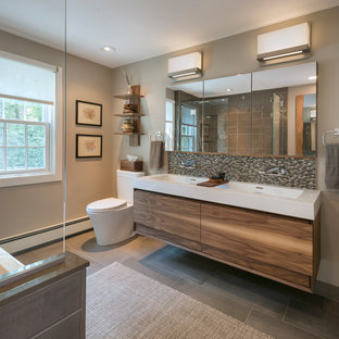 Example of a mid-sized transitional master gray tile and porcelain tile porcelain floor and gray floor bathroom design in Boston with flat-panel cabinets, medium tone wood cabinets, a one-piece toilet, beige walls, a trough sink, solid surface countertops and white countertops