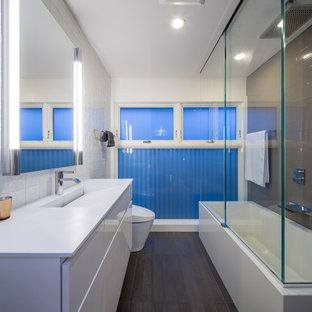 Imagen de cuarto de baño moderno con lavabo integrado, armarios con paneles lisos, puertas de armario blancas, baldosas y/o azulejos grises y encimeras blancas