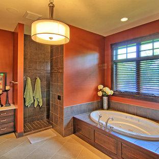 他の地域の大きいトランジショナルスタイルのおしゃれなマスターバスルーム (シェーカースタイル扉のキャビネット、濃色木目調キャビネット、ドロップイン型浴槽、アルコーブ型シャワー、分離型トイレ、茶色いタイル、セラミックタイル、赤い壁、トラバーチンの床、オーバーカウンターシンク、クオーツストーンの洗面台、ベージュの床、オープンシャワー、ベージュのカウンター) の写真
