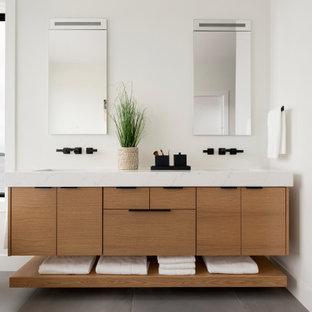 Foto på ett mellanstort funkis vit en-suite badrum, med släta luckor, beige skåp, ett fristående badkar, en kantlös dusch, en toalettstol med hel cisternkåpa, vita väggar, cementgolv, ett undermonterad handfat, marmorbänkskiva, grått golv och med dusch som är öppen