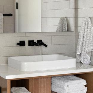 Bild på ett mellanstort funkis vit vitt badrum för barn, med släta luckor, skåp i ljust trä, en kantlös dusch, en vägghängd toalettstol, vit kakel, keramikplattor, vita väggar, klinkergolv i keramik, ett nedsänkt handfat, marmorbänkskiva, flerfärgat golv och dusch med gångjärnsdörr