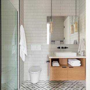ミネアポリスの中くらいのコンテンポラリースタイルのおしゃれな子供用バスルーム (フラットパネル扉のキャビネット、淡色木目調キャビネット、バリアフリー、壁掛け式トイレ、白いタイル、セラミックタイル、白い壁、セラミックタイルの床、オーバーカウンターシンク、大理石の洗面台、マルチカラーの床、白い洗面カウンター、洗面台1つ、フローティング洗面台) の写真