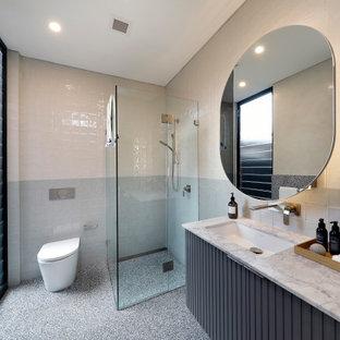 Modern inredning av ett mellanstort vit vitt badrum med dusch, med möbel-liknande, grå skåp, ett undermonterat badkar, flerfärgad kakel, flerfärgade väggar, terrazzogolv, ett undermonterad handfat och marmorbänkskiva