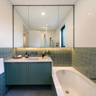 This is an example of a mid-sized contemporary kids bathroom in Sydney with shaker cabinets, green cabinets, an undermount tub, terrazzo floors, an undermount sink, engineered quartz benchtops, white benchtops, a single vanity, a floating vanity, green tile, a corner shower and white walls.