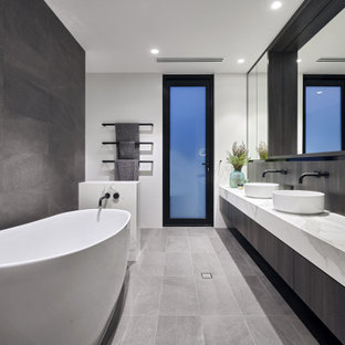 Contemporary master bathroom in Perth with a freestanding tub, gray tile, marble benchtops, a double vanity, flat-panel cabinets, grey cabinets, white walls, a vessel sink, grey floor, white benchtops and a floating vanity.