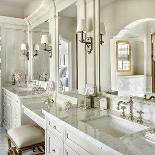 Foto de cuarto de baño mediterráneo con lavabo bajoencimera, puertas de armario blancas, paredes blancas y armarios con paneles con relieve