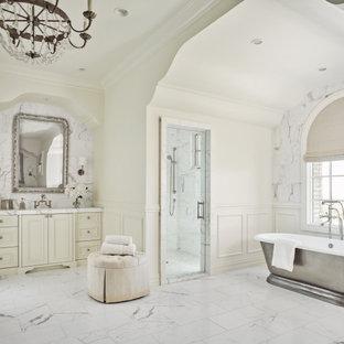 Bild på ett medelhavsstil vit vitt en-suite badrum, med marmorgolv, luckor med infälld panel, vita skåp, ett fristående badkar, våtrum, vita väggar, ett undermonterad handfat, vitt golv och dusch med gångjärnsdörr