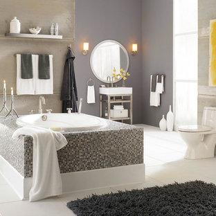 Esempio di una stanza da bagno padronale tradizionale di medie dimensioni con WC monopezzo, piastrelle grigie, nessun'anta, vasca da incasso, piastrelle di cemento, pareti grigie, pavimento con piastrelle in ceramica, lavabo a consolle, top in superficie solida e pavimento bianco