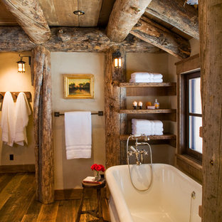 На фото: ванная комната в стиле рустика с отдельно стоящей ванной, коричневыми стенами и темным паркетным полом с