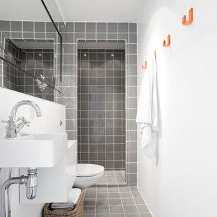 Inspiration för ett mellanstort minimalistiskt badrum, med släta luckor, vita skåp, en vägghängd toalettstol, grå kakel, vita väggar, klinkergolv i keramik, ett väggmonterat handfat och keramikplattor