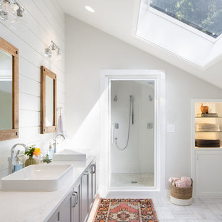 Example of a large coastal master porcelain floor and white floor bathroom design in Seattle with shaker cabinets, gray cabinets, a vessel sink, white countertops, white walls, marble countertops and a hinged shower door