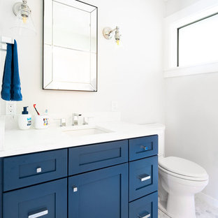 Imagen de cuarto de baño con ducha, marinero, de tamaño medio, con armarios estilo shaker, puertas de armario azules, sanitario de dos piezas, paredes blancas, suelo de mármol, lavabo bajoencimera, encimera de acrílico, suelo gris y encimeras blancas