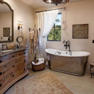 Modelo de cuarto de baño principal, campestre, con lavabo bajoencimera, armarios tipo mueble, puertas de armario de madera oscura, bañera exenta, paredes beige y suelo de cemento