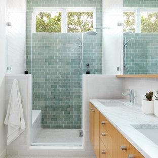Cette photo montre une grand douche en alcôve principale tendance avec un placard à porte plane, des portes de placard en bois clair, des carreaux de céramique, un sol en carrelage de céramique, un lavabo encastré, un plan de toilette en marbre, une cabine de douche à porte battante, un banc de douche, meuble double vasque, meuble-lavabo suspendu, un carrelage vert, un mur blanc, un sol blanc et un plan de toilette blanc.