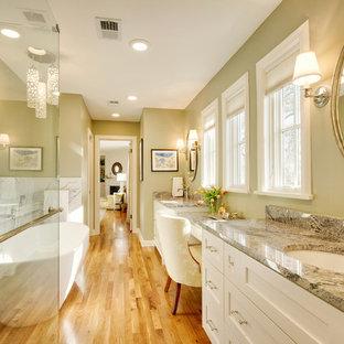 Inredning av ett klassiskt mycket stort en-suite badrum, med skåp i shakerstil, vita skåp, ett fristående badkar, en toalettstol med separat cisternkåpa, grön kakel, keramikplattor, gröna väggar, mellanmörkt trägolv, ett undermonterad handfat, granitbänkskiva, brunt golv och dusch med gångjärnsdörr