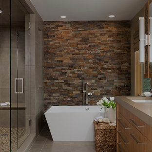 Trendy slate tile freestanding bathtub photo in Detroit with an undermount sink, flat-panel cabinets, medium tone wood cabinets and brown countertops