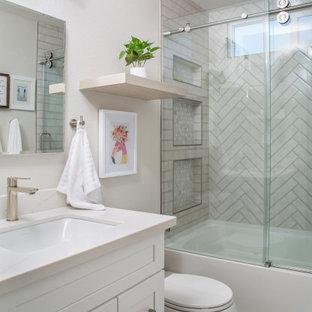 Foto på ett litet vintage vit badrum med dusch, med skåp i shakerstil, vita skåp, ett platsbyggt badkar, en dusch/badkar-kombination, en toalettstol med hel cisternkåpa, grå kakel, tunnelbanekakel, vita väggar, laminatgolv, ett undermonterad handfat, bänkskiva i kvarts, brunt golv och dusch med skjutdörr