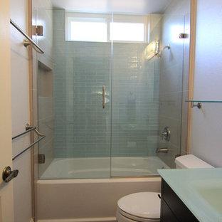 Modern inredning av ett litet badrum, med ett integrerad handfat, släta luckor, skåp i mörkt trä, bänkskiva i glas, ett badkar i en alkov, en dusch/badkar-kombination, en toalettstol med separat cisternkåpa, blå kakel, glaskakel, blå väggar och klinkergolv i porslin