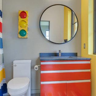 Exemple d'une petit salle de bain tendance pour enfant avec des portes de placard rouges, un mur gris, un sol en carrelage de céramique, un lavabo encastré, un plan de toilette en granite, un placard à porte plane, un WC à poser et un sol gris.