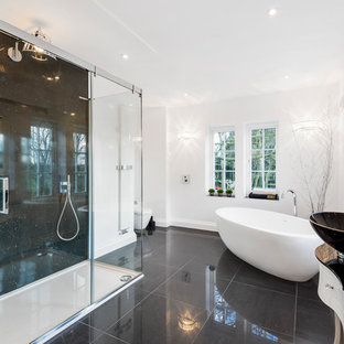 Photo of a large contemporary family bathroom in West Midlands with a freestanding bath, a double shower, a wall mounted toilet, white walls, a console sink, black floors, a sliding door and black worktops.