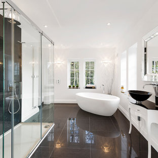 Large contemporary ensuite bathroom in West Midlands with freestanding cabinets, white cabinets, a freestanding bath, black tiles, white walls, porcelain flooring, a console sink, glass worktops, black floors, a corner shower and a sliding door.