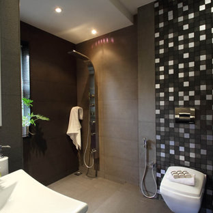 Trendy gray tile and stone tile concrete floor walk-in shower photo in Bengaluru with a wall-mount toilet and gray walls