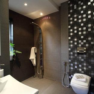 Idéer för funkis badrum, med en vägghängd toalettstol, en kantlös dusch, grå kakel, stenkakel, grå väggar och betonggolv